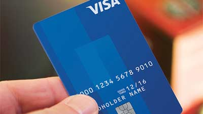 Close up of blue Visa Card being held up by a person.